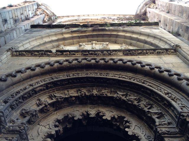 Perspectiva de las arquivoltas, del tímpano y, más arriba, el rosetón, todo ello flanqueado por sendas torrecillas defensivas. FOTO: J.M.G.