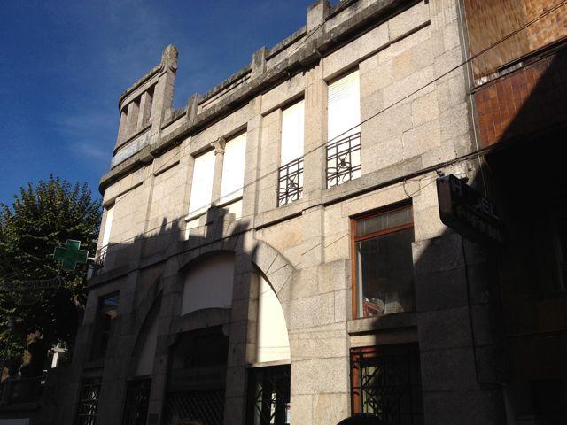Vista de la fachada con la puerta de acceso a la farmacia bajo un gran arco. FOTO: J.M.G.